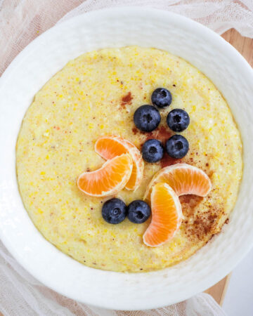 Cornmeal porridge in white bowl topped with blueberries and orange slices.