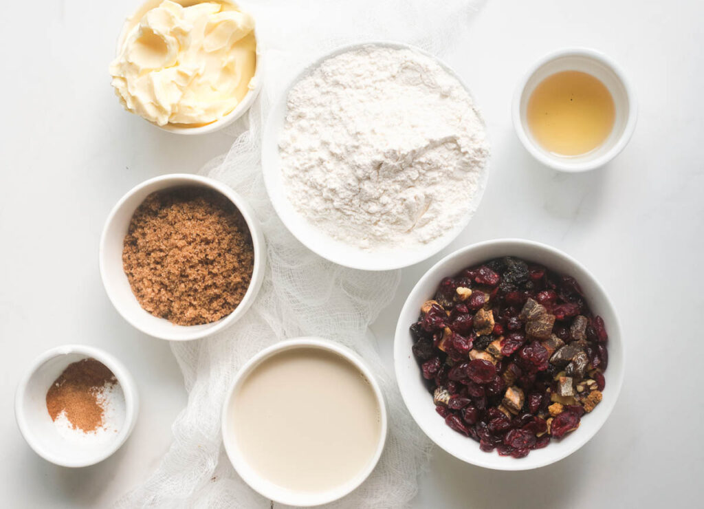Ingredients for vegan fruit cake: vegan butter, flour, dried fruit and nuts, vanilla extract, vegan buttermilk, brown sugar, and spices.
