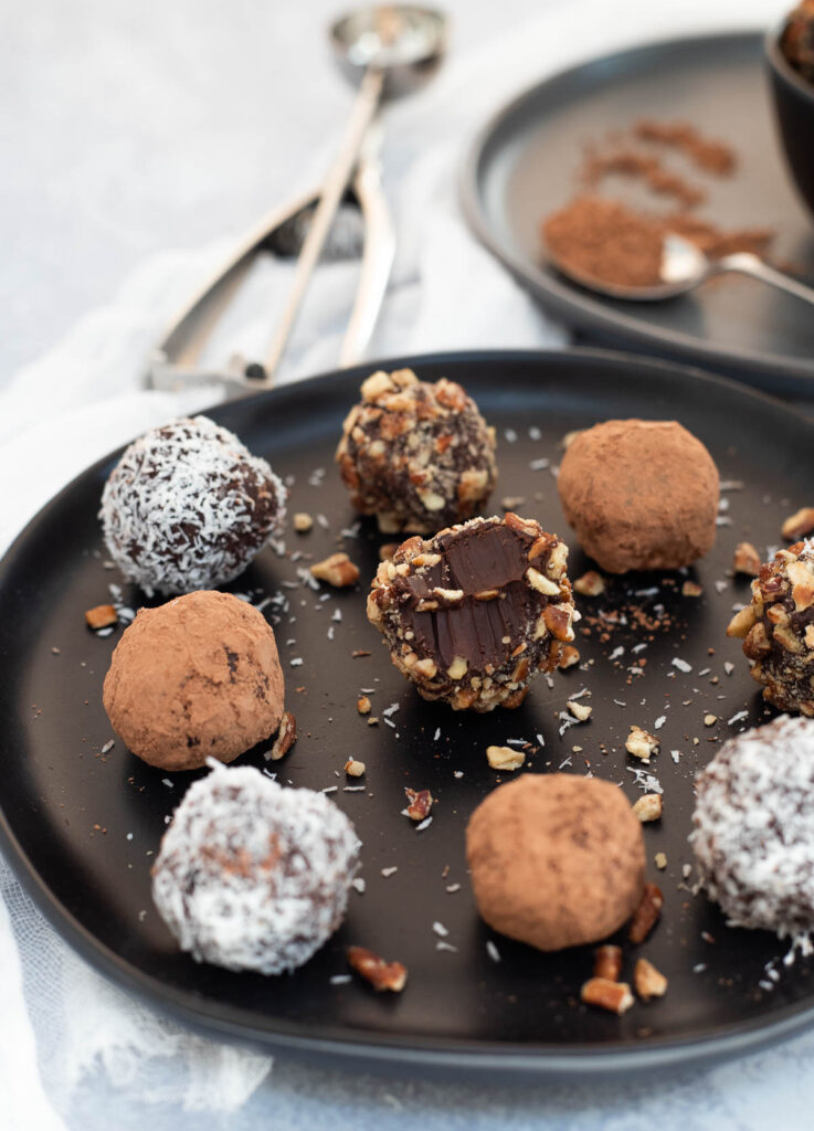 Chocolate vegan truffles coated in nuts, cacao powder, and coconut on black plate (one in the center has a bite taken out).