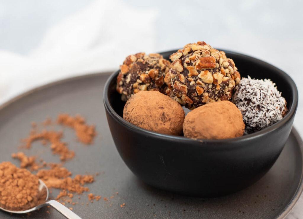 Chocolate vegan truffles in black bowl.