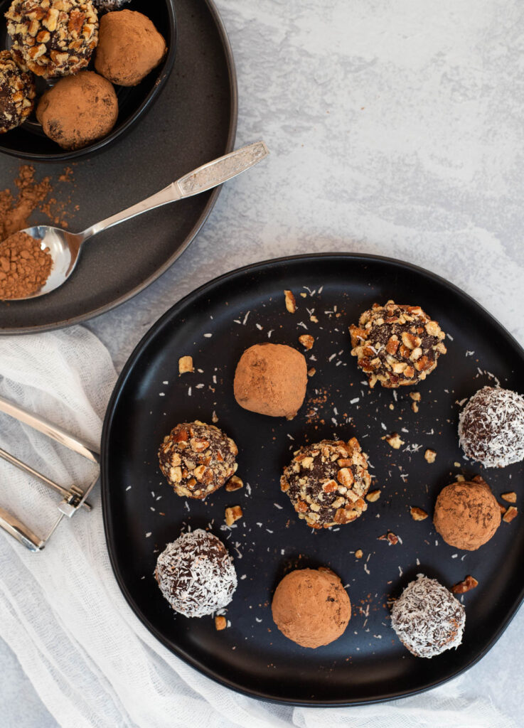 Chocolate vegan truffles coated in nuts, cacao powder, and coconut on black plate.