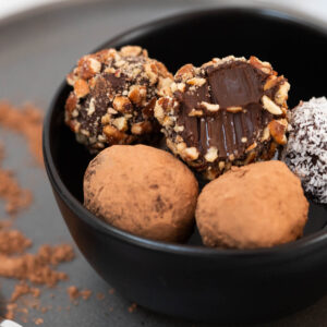 Chocolate vegan truffles coated in nuts, cacao powder, and coconut in small black bowl.