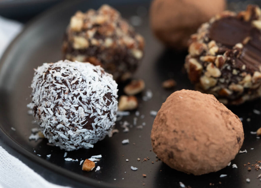 Chocolate truffles on black plate coated in nuts, coconut flakes, and cacao powder.
