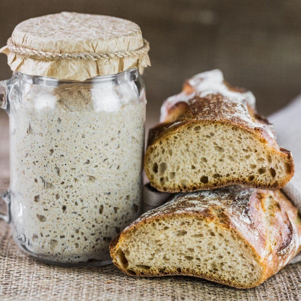 Sourdough bread beside sourdough starter.