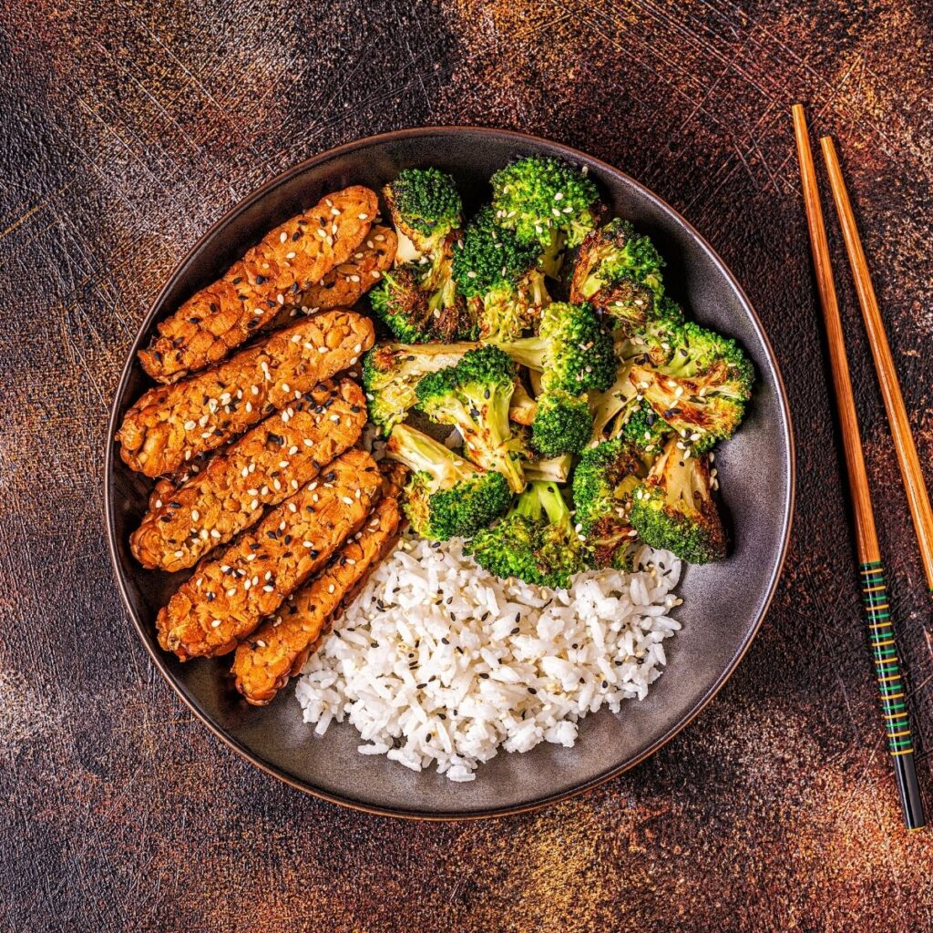Sliced tempeh, broccoli, and rice in bowl served with chopsticks.